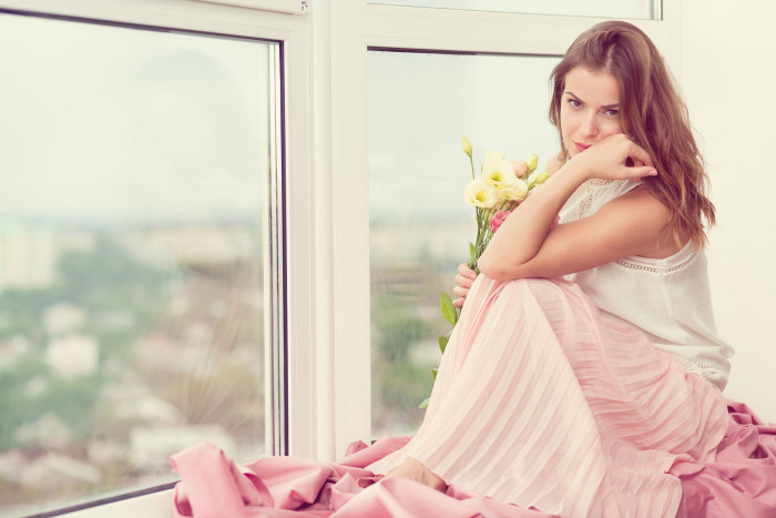 42612716 - romantic girl in long gown sitting by the window